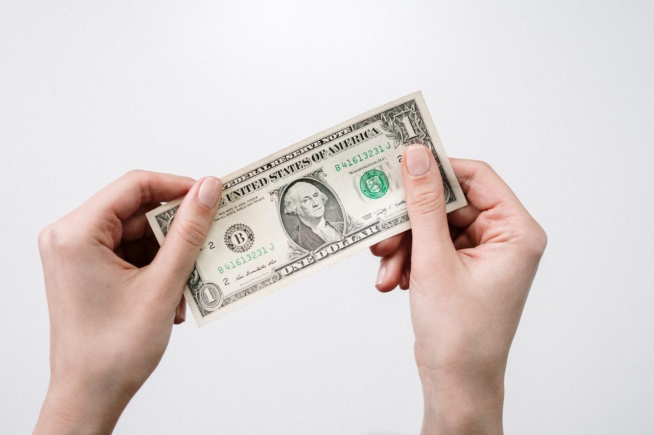 Hand holding a dollar bill